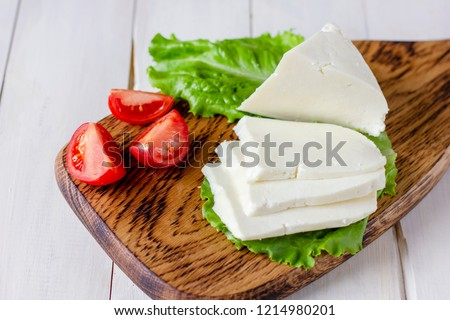 Homemade Adyghe cheese with spices on wooden board with fresh vegetables