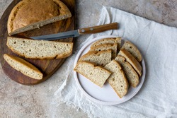 Homemade almond Low carb ketogenic bread with bran and fiber on plate, Wooden Cutting Board with knife, light linen napkin on beige stone concrete background. glutenfree vegetarian food concept.