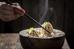 Homemade and hot manti dumplings in wooden bowl