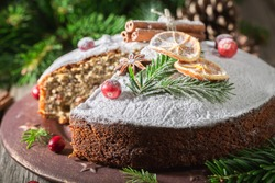 Homemade and tasty poppy seed cake for Christmas decorated with orange and spruce