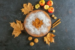 Homemade apple pie, cobbler, charlotte with walnut and cinnamon. Thanksgiving dish and fall dry leaves on rustic table. Autumn harvest festival. Copy space for text, tonned