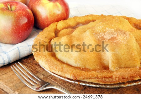 Homemade apple pie fresh from the oven on a rustic wood surface.