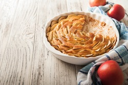 Homemade apple pie on a white wooden background near the window close-up and copy space. Charlotte in the morning on the table.