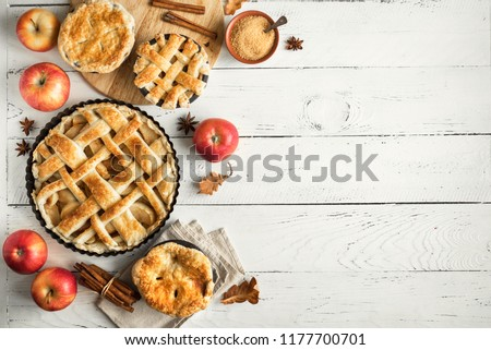 Homemade Apple Pies on white wooden background, top view. Classic autumn Thanksgiving dessert - organic apple pie.