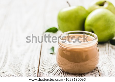 Homemade applesauce in glass jar and green apples on shabby white wooden background. Selective focus, space for text.  stock photo