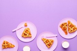 Homemade apricot pie slices on pink plates, on purple background. Flat lay of fruit tart with lattice crust. Summer dessert. Thanksgiving pie portions