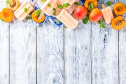 Homemade apricot popsicles, fruity lollypop non-dairy vegan apricot gelato, on grey old wooden background copy space top view