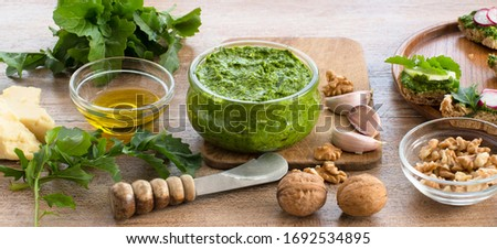 Homemade arugula pesto and ingredients on a wooden table Zdjęcia stock ©
