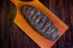 Homemade Australian bread with dark wholemeal flour on a wooden cutting board