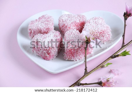 Homemade Australian style pink heart shape small lamington cake on heart shape white plate with spring blossom on a pink background. Closeup.