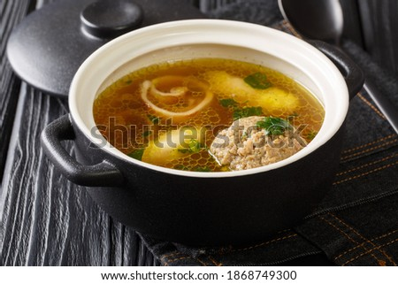 Homemade Austrian rindsuppe based on beef broth with dumplings close-up in a saucepan on the table. horizontal Сток-фото ©