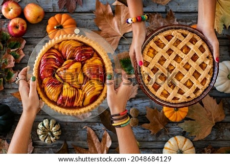 Homemade autumn pies at the hands of two women. Overhead view of an apple pie, a pumpkin pie and a peach pie