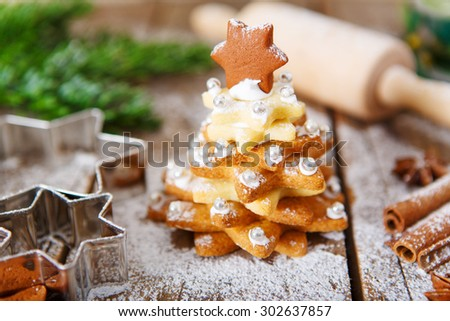 Homemade baked Christmas gingerbread tree on vintage wooden background. Anise, cinnamon, baking roll, star forms and decoration utensils. With icing sugar snow. Selfmade gift for xmas.