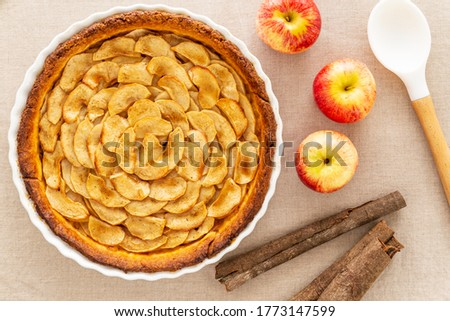 Homemade baked French apple tart, an open faced apple pie, in a baking white ceramic dish aside Gala red apples, cinnamon sticks and white cooking spoon, all on a natural linen table cloth. Flat lay