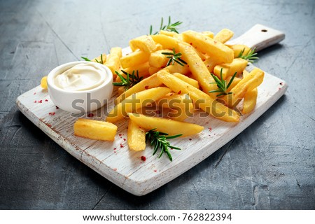 Photo of  Homemade Baked Potato Fries with Mayonnaise and rosemary on white wooden board