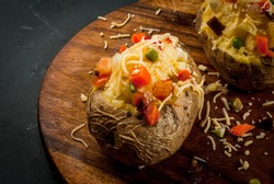 Homemade baked potato with cheese and vegetables, copy space, close view