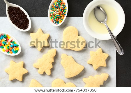 Homemade baked sugar cookies for Christmas with icing and sprinkles on the side, photographed overhead on slate #754337350