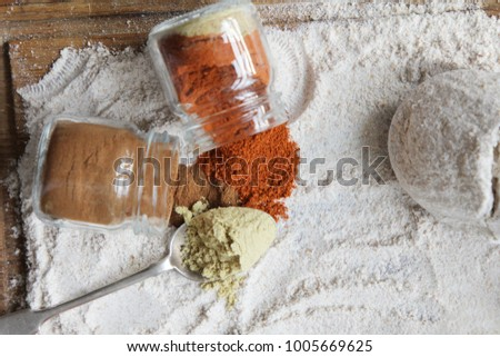 Homemade baking, cooking process. Flour and spices cinnamon, red pepper and dry ginger on a rustic wooden kitchen board #1005669625
