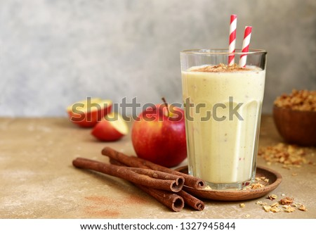 Homemade banana apple smoothie or lassi with cinnamon and oats in a tall glass on a light slate, stone or concrete background