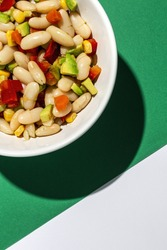 homemade bean salad with carrots, avocado, Purple cabbage, pepper,corn and olive oil and lemon juice on colorful background. Vegan food.Healthy food concept