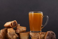 Homemade Beef Bone Broth in mug on dark background. Selective focus, copy space. Bones contain collagen, which provides the body with amino acids, which are building blocks of proteins.