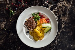Homemade beef steak served over thin baked potatoes.Small portion.Portion control.Restaurant recipe recreation.Diet ingredients.Cooking food at home.Healthy nutritious dinner for single person.