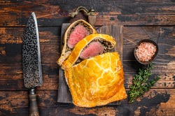 Homemade Beef Wellington puff pie with tenderloin meat on a cutting board. Dark wooden background. Top view.