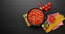 Homemade boiling italian pasta with tomato sauce in cast iron pan served with red chili pepper, fresh basil, cherry-tomatoes and spices over black rustic wooden background, cooking food concept