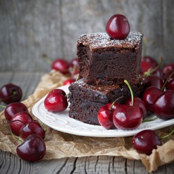 Homemade brownies with fresh berry on old wooden background, selective focus