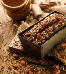 Homemade buckwheat bread with the addition of nuts and seeds in a baking tin on a wooden table. Gluten-free bread