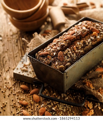 Homemade buckwheat bread with the addition of nuts and seeds in a baking tin on a wooden table. Gluten-free bread Foto d'archivio ©