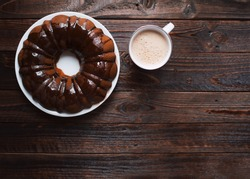 Homemade Bundt cake with chocolate icing, cup of hot coffee on a dark wooden table. Top view.