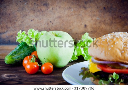 Homemade burger made from fresh vegetables and beef versus fresh fruit and vegetables on wooden background. Healthy and unhealthy food.