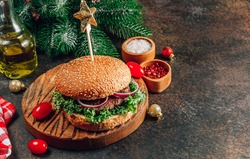 Homemade burger with black angus beef meat and fresh vegetables on a wooden board with Christmas decoration. Selective focus with copy space