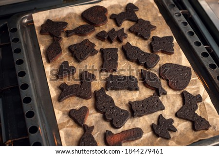 Photo of  Homemade burnt black cookies on the iron baking sheet. Baking Christmas cookies, shortbread, failure.
