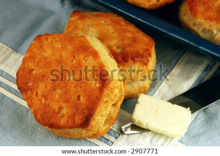 Homemade buttermilk biscuits with butter on a vintage blue table linen