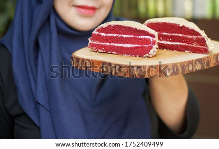 "Homemade cake ""Red Velvet"" decorated with cream. Red velvet cake on a cutting board. Red velvet cake on wood board. Red velvet cake with nature background."