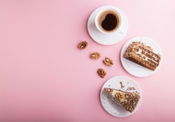 Homemade cake with milk cream and walnuts with cup of coffee on a pink pastel background. top view, flat lay, copy space.