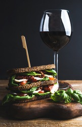 Homemade caprese sandwich and glass of red wine on wooden board, dark background, selective focus, vertical composition