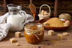 Homemade caramel sauce and ingredients on wooden table. Brown sugar, cream, butter
