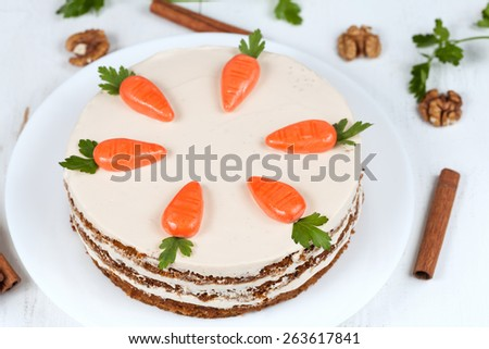 Homemade carrot cake with little carrots on top on white background