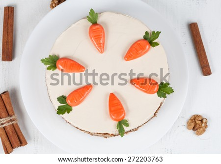 Homemade carrot sponge cake with little carrots and  cream on white background