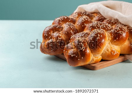 Homemade Challah bread with white cover, Jewish cuisine. Decorated with sesame and poppy seeds. Light green background. Stok fotoğraf ©