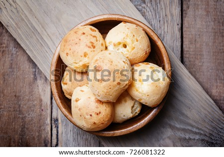 Homemade cheese buns in bowl. vintage wooden background, top view