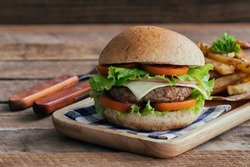 Homemade cheese burger or hamburger on wood plate served with french fries put on wood table with copy space. Fast food for breakfast or lunch.
