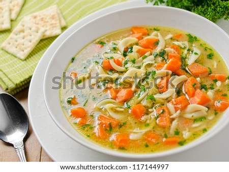 Homemade chicken noodle soup with crackers.
