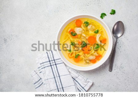 Homemade chicken soup with noodles and vegetables in a white bowl, white background. Healthy warm comfortable food.