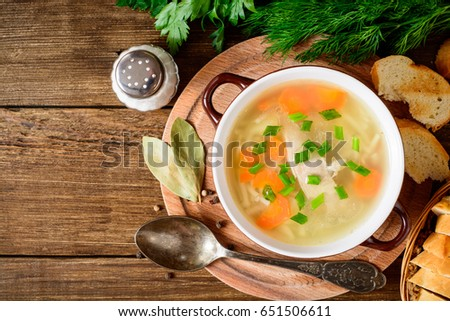Shutterstock Homemade chicken soup with noodles and vegetables in ceramic bowl on wooden table. Top view.