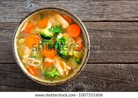 Homemade chicken vegetable soup, overhead, close up view on an old wood background #1007551606