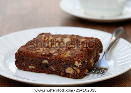Stock Photo Homemade chocolate brownie with hazelnuts on white plate with fork and cup in background